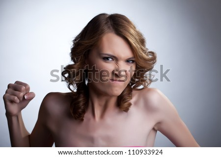 Aggressive young woman clench one's fist - stock photo