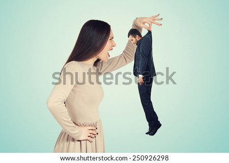 aggressive young woman holding small man and screaming at him. photo over blue background - stock photo