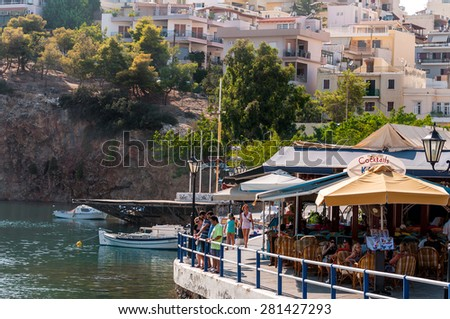 AGHIOS NIKOLAOS - AUGUST 2013: Cafe with tourists near lake at port of Aghios Nikolaos on Crete island, Greece.