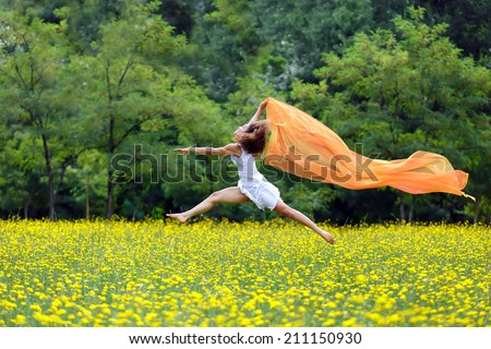 Agile barefoot woman with curly brown hair leaping in the air in a meadow of yellow wildflowers trailing a colorful orange scarf in the breeze as she celebrates her freedom and the beauty of nature - stock photo