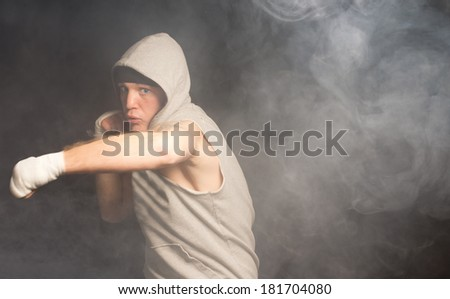 Agile young boxer throwing his weight behind a punch with a look of grim dtermination in a smoky dark environment - stock photo