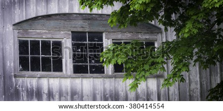 Aging barns of the Midwest were more than farm buildings, many had beautiful architectural features such as this grouping of windows with an arch detail. - stock photo