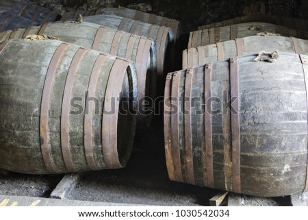 Aging old wooden barrels and casks in cellar at whisky distillery in Scotland.