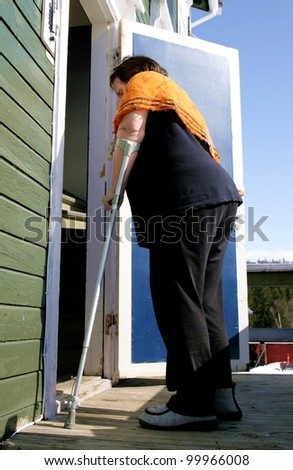 Aging, overweight disabled woman with crutch entering her shabby old house. - stock photo