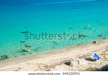 Agios Nikitas beach in Lefkada Island, Greece - Ionian Islands. In the background it is visible the village of Agios Nikitas. The beach is near the village of Agios Nikitas.
