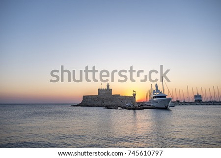 Agios Nikolaos fortress on the Mandraki harbour of Rhodes Greece at sunrise