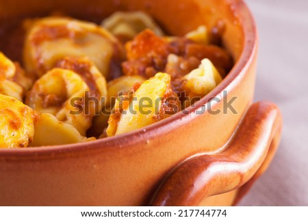 Agnolotti with tomato sauce in crock pot, close up - stock photo