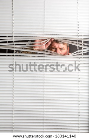 Agoraphobia. A man looking through  a rain spotted window blinds with facial expressions.  - stock photo