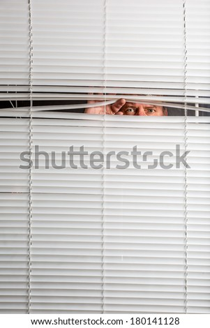 Agoraphobia. A man looking through a window blinds with facial expressions.  - stock photo