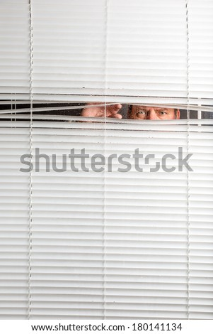 Agoraphobia. A man looking through rain spotted window blinds with facial expressions.  - stock photo