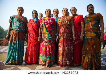 AGRA, INDIA - APRIL 24 : A group of finely dressed Indian females pose for a group photo near the Taj Mahal in Agra on 24 April, 2013. Domestic tourism is a booming market for many local businesses.