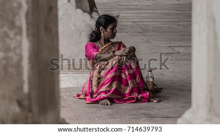 Agra, India - 15 July, 2017: Woman in pink sari sitting by herself