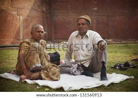 AGRA, INDIA - NOVEMBER 18:  Indian Wife and Husband resting near Agra Fort, during holy festival , Nov. 18, 2012.  Agra is the ancient city, attracting Indians from all over the subcontinent.