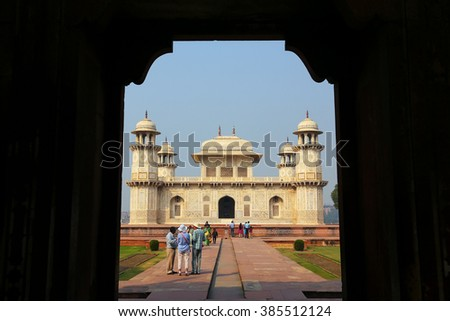 AGRA, INDIA - NOVEMBER 6: Unidentified people stand near Itimad-ud-Daulah Tomb on November 6, 2014 in Agra, India. This Tomb is often regarded as a draft of the Taj Mahal. - stock photo