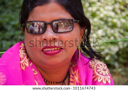 Agra, Uttar Pradesh, India - October 30 2014 : Woman in pink sari with matching pink lipstick and a gold tooth