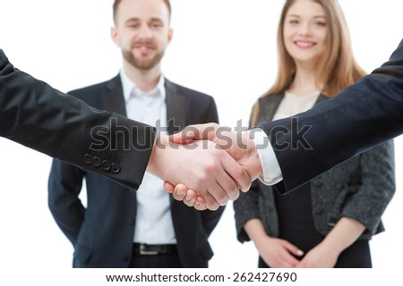 Agreement and congratulations. Close up of two businessmen shaking hands  with partners in the background. Focus on hands. Isolated on white. - stock photo