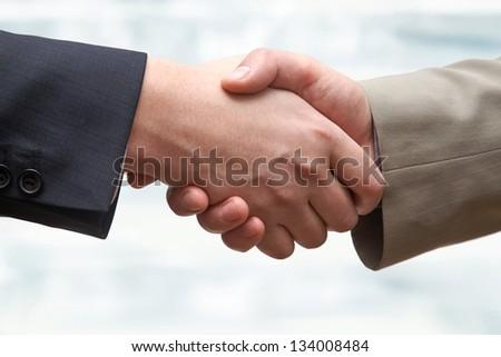 Agreement: business partners making handshake - stock photo