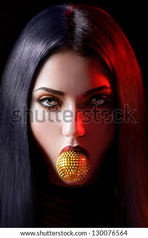 Agressive woman with a golden toy in the mouth on a black background