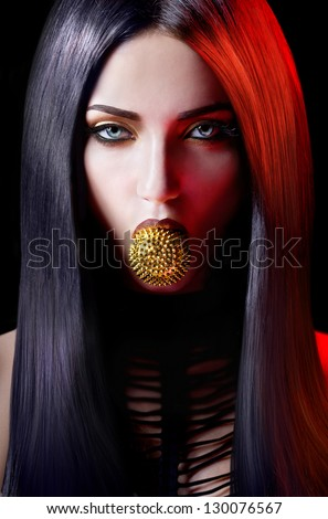 Agressive woman with a spiky toy in the mouth on a black background