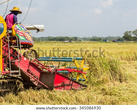 agricultural activities with combine harvesting machine in wheat crops - stock photo