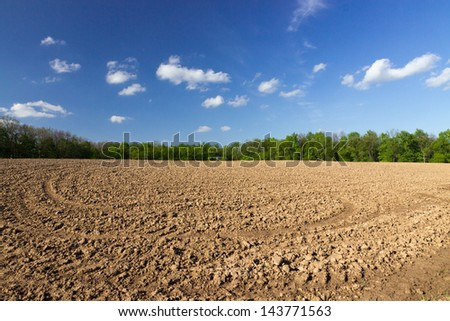agricultural black field plowing under blue sky clouds.