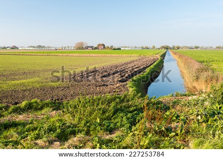 Agricultural Dutch polder landscape in autumnal colors with a  ditch reflecting the blue sky and in the background the edge of a small village. - stock photo