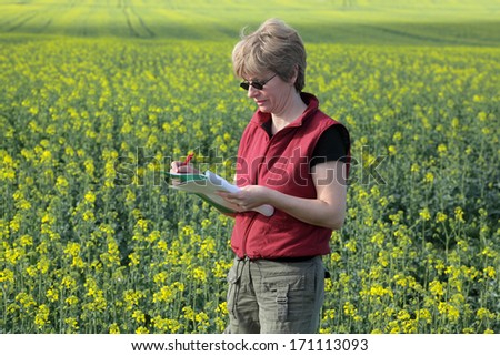 Agricultural expert inspecting quality of oil rape