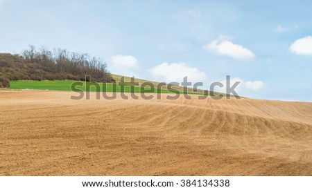 Agricultural field with soil and blue sky - stock photo