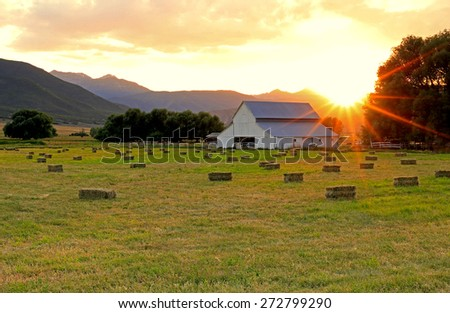 Agricultural landscape with a barn and hay bales in a field, Utah, USA. - stock photo