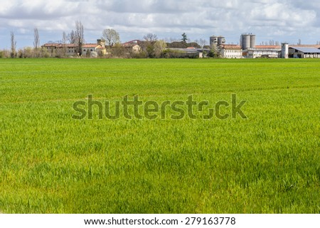 Agricultural landscape with farm and silos and a sky with clouds - stock photo