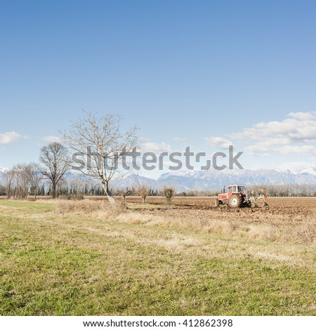 Agricultural landscape. With tractor plowing a field. The mountains in the background. - stock photo