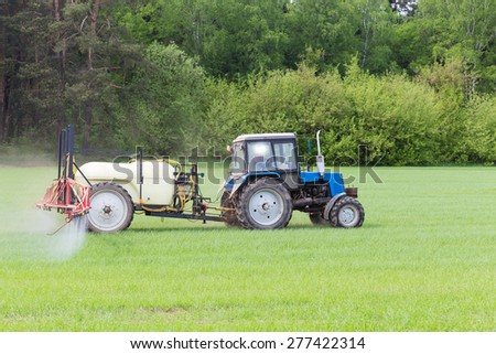 agricultural machine fertilizes a green field in spring - stock photo