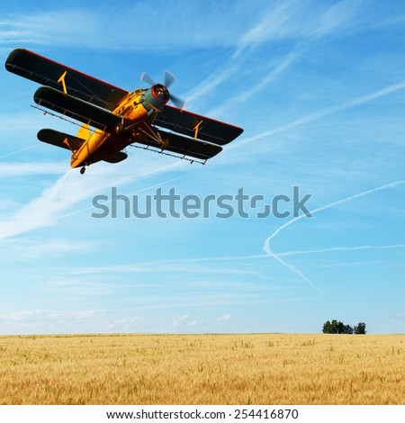 Agricultural plane spraying crops. - stock photo
