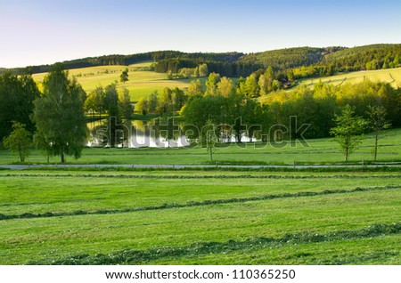 Agricultural scenery with pond and blue sky - stock photo
