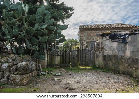 Agricultural terrain with old rural cottage on Majorca in Spain  Typical abandoned finca with stone hut and wooden fence and big green cactus - stock photo