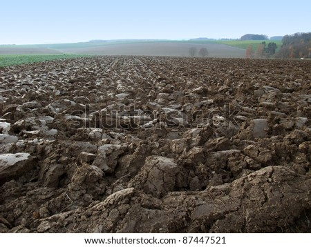 agricultural theme showing a low angle shot of a plowed field in Southern Germany at autumn time - stock photo