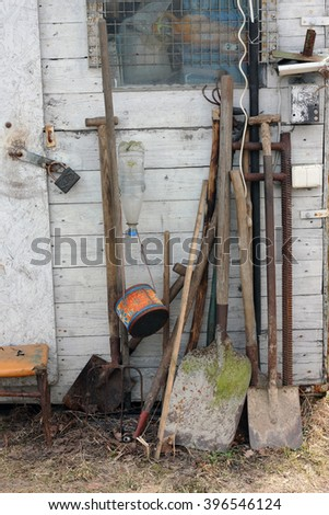 Agricultural tools - shovels, a pitchfork, a rake and a mattock near a rural shed. On the earth it is possible to notice a dead polecat. - stock photo