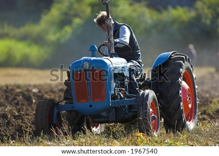 Agricultural Tractor ploughing a field - stock photo