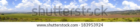 Agricultural valley spring panoramic view - green fields,arable land, sleeping vineyards,olive plantations, blossom flowers and meliorative reservoirs - Ayalon valley, Judaic mountains, Israel  - stock photo