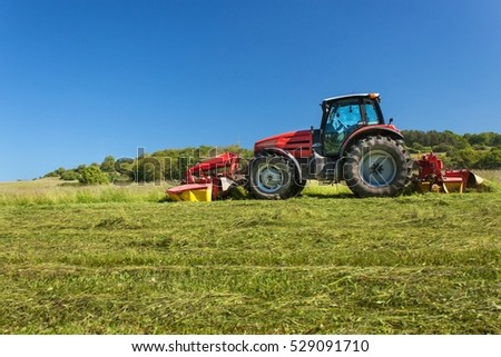 Agricultural work. Red tractor mowing the meadow, Czech Republic. Farmer harvested hay.