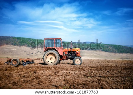 agriculture and harvesting - Vintage tractor plowing and cultivating the field under the blue sky