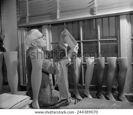 Agriculture Department fabric technician examines the cotton stockings that would replace those made by Japanese silk, after FDR froze all Japanese credits in the United States. July 1941. - stock photo