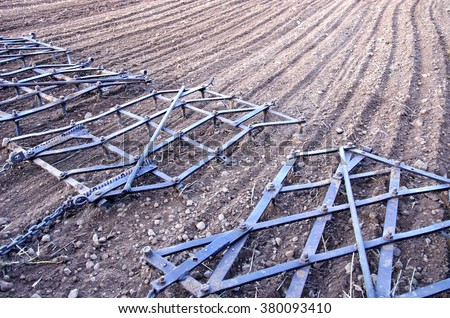 Agriculture machinery metal harrow rake on plowed farm field - stock photo