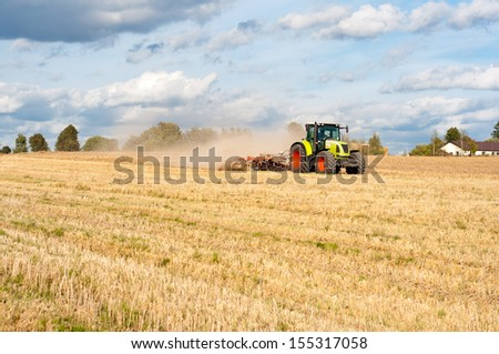 Agriculture tractor on field on job.