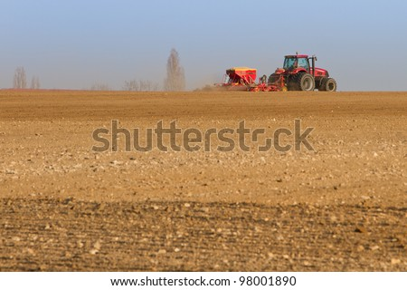 Agriculture tractor sowing seeds and cultivating field (focus on tractor) - stock photo
