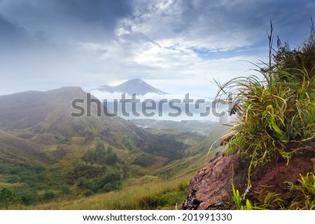 Agung volcano and lake view from Batur crater in cloudy weather, Bali, Indonesia - stock photo