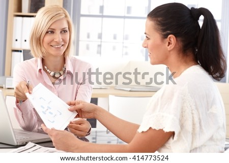 aHappy blonde casual secretary having a work meeting at business office, with chart and pen in hand.
