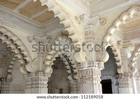 AHMEDABAD, GUJARAT, INDIA - AUGUST 21 : Hutheesing Jain Temple on August 21, 2012 in Ahmedabad. Beautiful archs with ornamental stone carving on the colonnaded columns. - stock photo