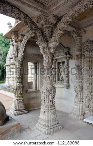 AHMEDABAD, GUJARAT, INDIA - AUGUST 21 : Hutheesing Jain Temple on August 21, 2012 in Ahmedabad. Ornated archs supported by decorative intricate stone carved columns of entrance, ' Mukhamandapa '. - stock photo