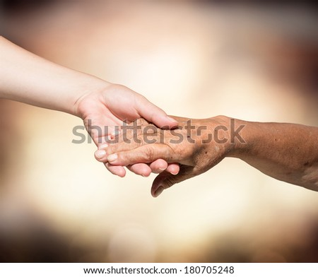 aid concept - problems elderly - hands of young and senior  - stock photo